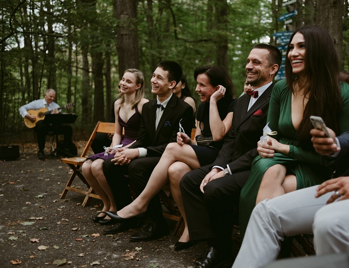 Wedding guests laughing and ceremony musician at Kortright Centre